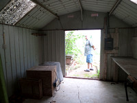 Paved floor of more shed off the back. greenhouse is behind.